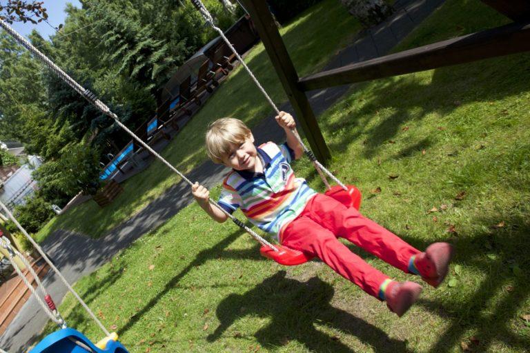 Dziecko na huśtawce na placu zabaw Villa Verdi Łeba